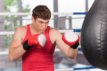 Boxer doing some training on punching bag at gym.