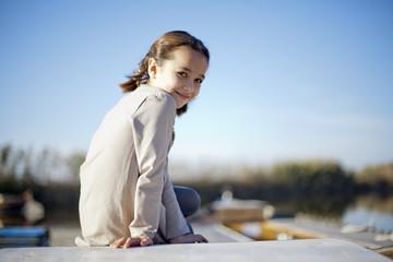 Niña sonriente con trenzas subida en barca