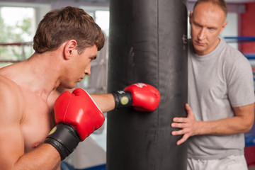 boxer and his coach doing some punching with bag.