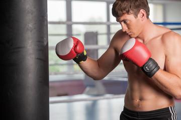Boxer doing some training on punching bag at gym.