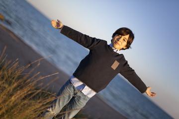 Niño con brazos en cruz con mar de fondo