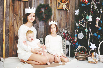 Three sisters posing in front of christmas tree