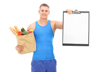 Young athlete holding grocery bag and a clipboard