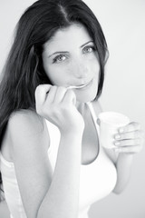 Beautiful woman enjoying white yogurt black and white portrait