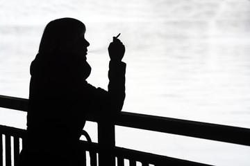 junge Frau raucht am Fluss, Silhouette, Berlin, Deutschland,