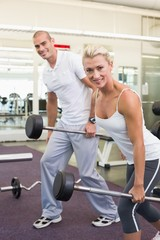 Sporty young couple lifting barbells in gym