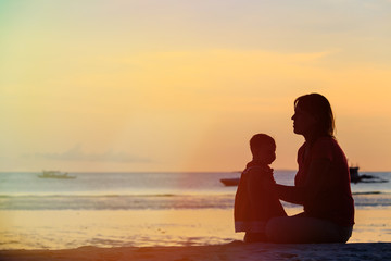 mother and little daughter on sunset beach
