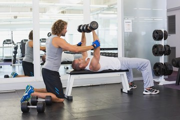 Male trainer assisting young man with dumbbells in gym