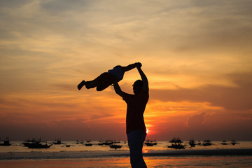 father and son silhouettes play at sunset