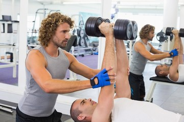 Male trainer assisting man with dumbbells in gym