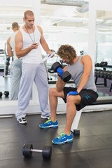Male trainer assisting man with dumbbell in gym