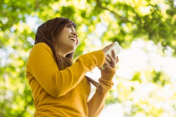 Beautiful young woman text messaging in park