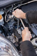 Mani che riparano um motore di automobile con una chiave