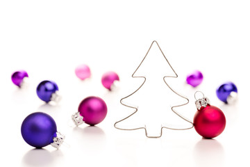 Christmas tree and baubles. Cookie cutter and colourful baubles.
