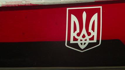 Ukrainian coat of arms onboard moored ship in harbor, emblem