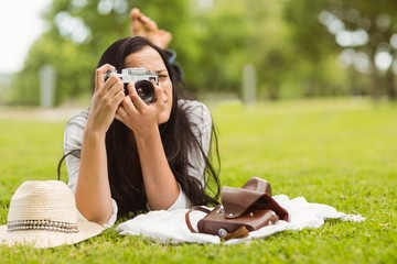 Brunette lying on grass taking picture