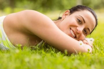Smiling brunette lying on grass
