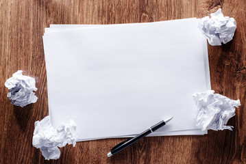 Blank Papers and Pen with Crumpled Papers on Sides