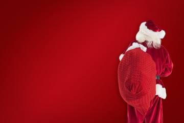 Composite image of santa is holding his bag in one hand