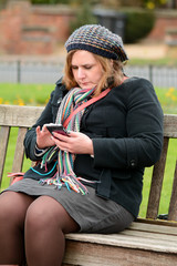 Woman checking mobile phone sat on wooden bench