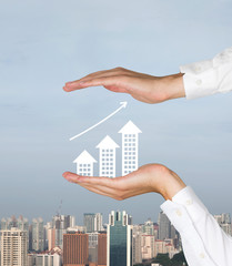 hands  holding paper buildings