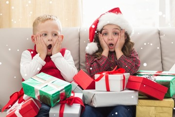 Composite image of festive siblings surrounded by gifts