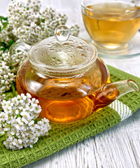 Tea with yarrow in glass teapot on board