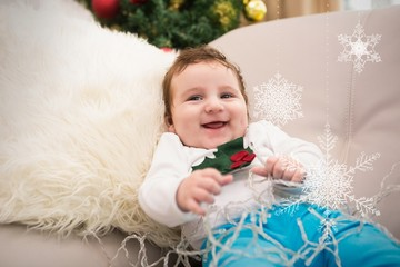 Composite image of cute baby boy on the couch at christmas