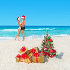 Couple in santa hats at tropical  beach with christmas tree and