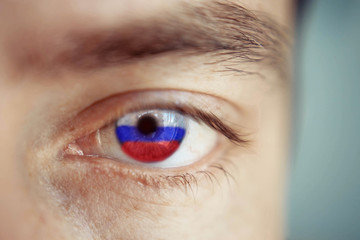 Men portrait with eyes the color of Russia flag