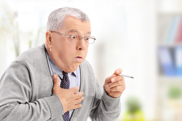Senior man choking from the smoke of a cigarette