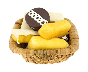 Junk food cakes and donuts in a wicker basket