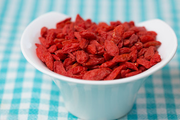 dried goji berries in white bowl on checked fabric