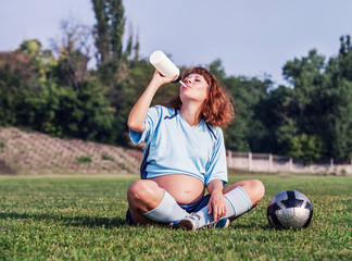 Pregnant woman drink on the soccer field