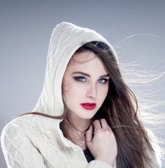 Beautiful charming woman in hood,  over blue background.