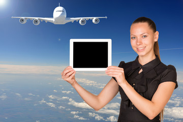 Beautiful businesswoman holding tablet PC. Blue sky, clowds and