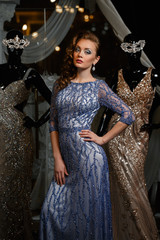 fashionable woman in blue dress with rhinestones and mannequins