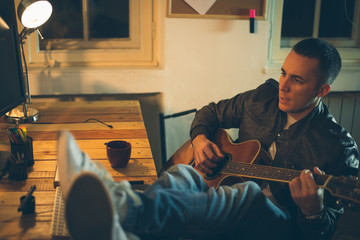 Man playing guitar at home after work