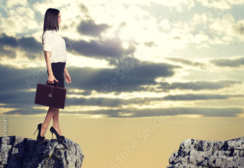 Businesswoman standing on the edge of rock gap - 74953475