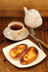 Two white toasts on white plate with cup of black tea