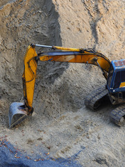 Excavator Loader with rised backhoe standing in sand
