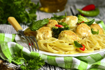 Spaghetti with chicken meatballs and broccoli.