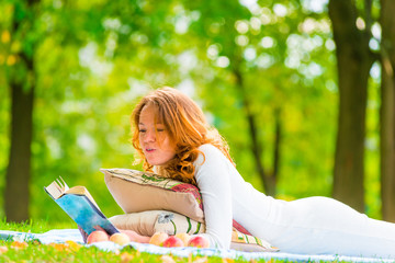 girl in white dress reading a book in the park