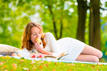 Red-haired student eats an apple and reading books in the park