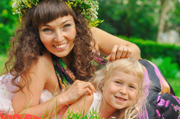 Girl and her mommy amid green grass
