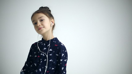 Child with earflaps dancing at studio background
