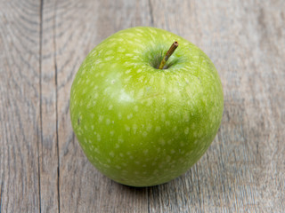 green apple placed on a wooden table