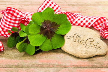 vierblättrige Kleeblätter, Geschenkband und Stein auf Holz