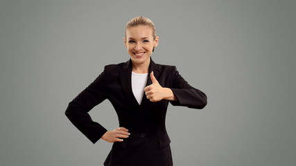 businesswoman presenting and shows thumb on grey background