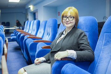 in the conference hall sits a smiling woman